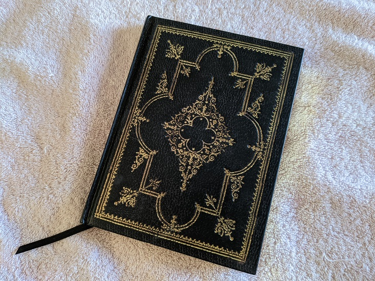 A black, hardcover journal on a pink towel. A black ribbon comes out from between the pages and trails off to the bottom left.